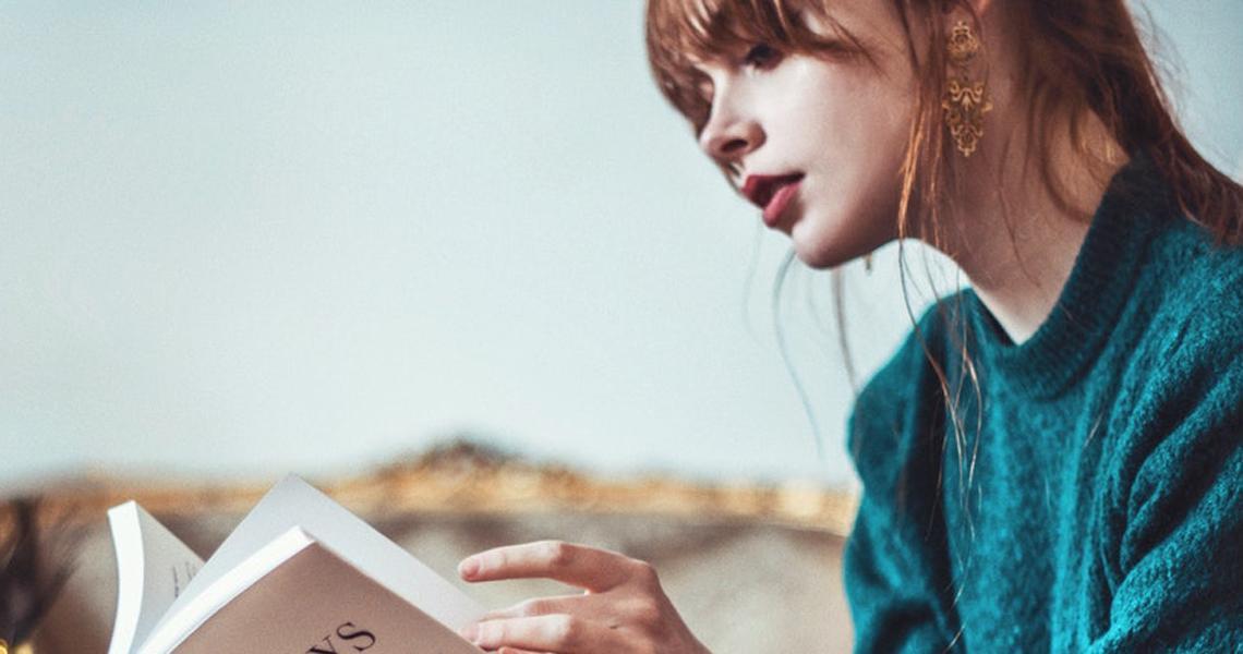 Chica leyendo un libro en sus manos