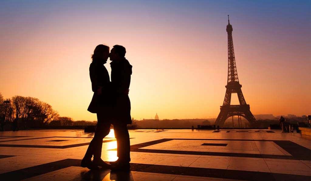 Pareja se besa frente a torre Eiffel